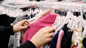 Vrouw die voor t-shirts winkelen stock footage