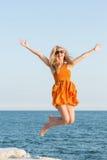 Vrouw die voor vreugde bij het overzees springen stock afbeelding