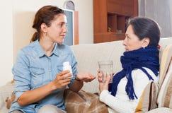 Vrouw die voor zieke rijpe moeder geeft royalty-vrije stock afbeeldingen