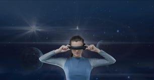 Vrouw die in VR-hoofdtelefoon tegen blauwe hemel met planeten en gloed kijken Stock Foto's