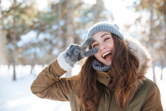 Vrouw die vredesteken in de winterpark tonen Royalty-vrije Stock Foto