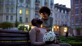 Vrouw die vriend koesteren, die met liefde kijken, die bloemen, romantische datum houden stock afbeeldingen
