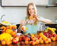 Vrouw die vruchten dranken maken Royalty-vrije Stock Afbeeldingen