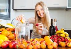 Vrouw die vruchten dranken met wijn maken Stock Afbeeldingen