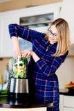 Vrouw die vruchten en groenten zetten in de eletrical mixer royalty-vrije stock foto's