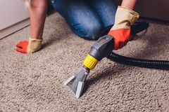 Vrouw die vuil verwijderen uit tapijt met stofzuiger in ruimte royalty-vrije stock fotografie