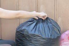 Vrouw die vuilniszak zetten in vuilnisbak Bind het om het gemakkelijk te maken zich te bewegen stock afbeelding