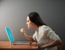 Vrouw die vuist tonen aan laptop Stock Foto's