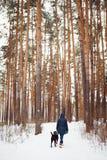 Vrouw die in warme kleren met hond spelen Royalty-vrije Stock Afbeeldingen