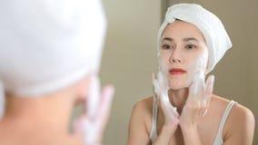 Vrouw die wassend haar gezicht met schuim in badkamers schoonmaken stock video