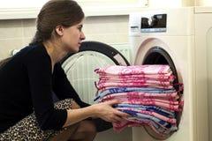 Vrouw die wasserij thuis zetten in wasmachine royalty-vrije stock foto's
