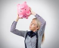 Vrouw die wat geld uit spaarvarken proberen te krijgen royalty-vrije stock afbeelding