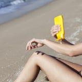 Vrouw die wat lotion aanzetten Stock Afbeeldingen