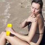 Vrouw die wat lotion aanzetten Stock Fotografie