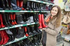 Vrouw die waterdichte schoenen in winkelcentrum kopen royalty-vrije stock foto's
