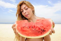 Vrouw die watermeloen op het strand eet Stock Afbeeldingen