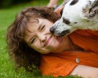 Vrouw die weerzinwekkend gezicht maken terwijl wordt gelikt door haar hond stock fotografie
