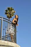 Vrouw die weg starend in afstand van balkon kijkt stock foto