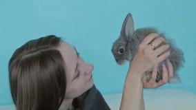 Vrouw die weinig leuk konijn houden stock videobeelden