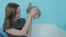 Vrouw die weinig leuk konijn houden stock footage