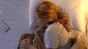 Vrouw die wekker op smartphone vroeg in ochtend, hoogste mening uitschakelen stock footage