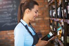 Vrouw die in wijnwinkel werken Stock Fotografie