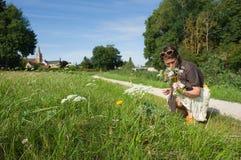 Vrouw die wilde bloemen plukt stock afbeeldingen