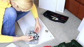 Vrouw die wit meubilair assembleren, haalt zij een schroef met een schroevedraaier aan stock footage