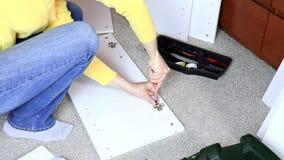 Vrouw die wit meubilair assembleren, haalt zij een schroef met een schroevedraaier aan stock video