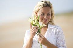 Vrouw die wit op de bloem van de strandholding draagt stock afbeeldingen