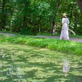 Vrouw die in witte kleding in het park op een de zomerdag lopen royalty-vrije stock foto's
