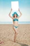 Vrouw die witte lege affiche op het strand houden Stock Foto