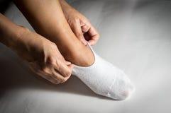 Vrouw die witte sok dragen aan voeten stock fotografie