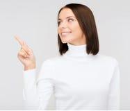 Vrouw die in witte sweater aan iets richten Stock Afbeeldingen