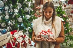 Vrouw die in witte warme wollen sweater een vakje stuk speelgoed glas decoratieve ballen in handen, exemplaarruimte houden Kerstm royalty-vrije stock afbeelding