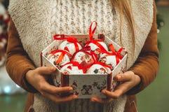 Vrouw die in witte warme wollen sweater een vakje stuk speelgoed glas decoratieve ballen in handen, exemplaarruimte houden Kerstm royalty-vrije stock foto