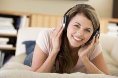 Vrouw die in woonkamer aan hoofdtelefoons luistert Royalty-vrije Stock Afbeeldingen