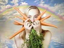 Vrouw die wortelen eet stock afbeelding