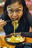Vrouw die yakisoba eten die naar camera kijken Stock Fotografie