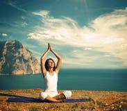 Vrouw die Yoga doen bij het Overzees en de Bergen stock afbeeldingen