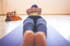 Vrouw die yoga doen bij houten vloer stock foto