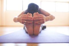 Vrouw die yoga doen bij houten vloer stock foto's