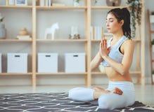 Vrouw die yoga doen, die in Lotus-positie thuis mediteren royalty-vrije stock afbeelding