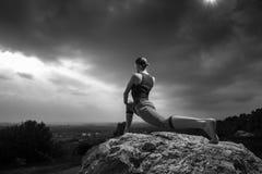 Vrouw die yoga doen tegen de het plaatsen zon Stock Foto