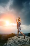 Vrouw die yoga doen tegen de het plaatsen zon Royalty-vrije Stock Afbeeldingen