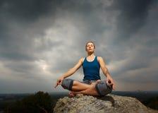 Vrouw die yoga doen tegen de het plaatsen zon Royalty-vrije Stock Foto's