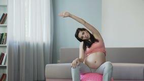 Vrouw die yoga doen tijdens zwangerschap om omloop en toonspieren te verbeteren stock videobeelden