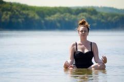 Vrouw die yoga in een water doen royalty-vrije stock afbeelding