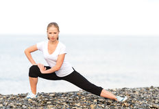 Vrouw die yoga en sportoefeningen op strand doen Stock Foto