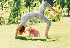 Vrouw die yoga met baby in aard doen royalty-vrije stock foto's